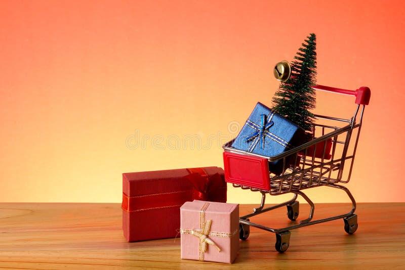 BEGREPPSMÄSSIGT NYTT ÅR med att shoppa spårvagnen, gåvaaskar och julgranen på en trätabell arkivbilder