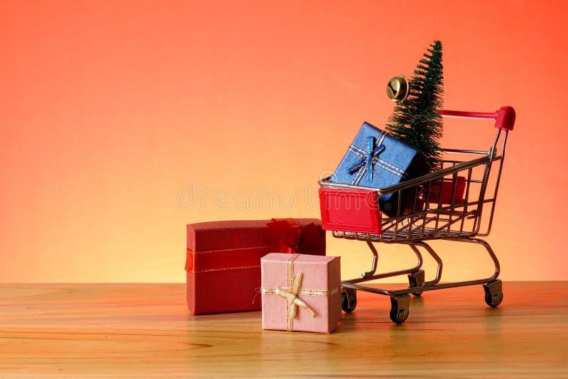 BEGREPPSMÄSSIGT NYTT ÅR med att shoppa spårvagnen, gåvaaskar och julgranen på en trätabell royaltyfri bild