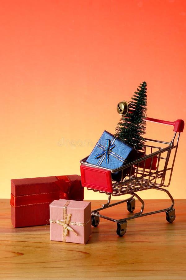BEGREPPSMÄSSIGT NYTT ÅR med att shoppa spårvagnen, gåvaaskar och julgranen på en trätabell royaltyfri foto