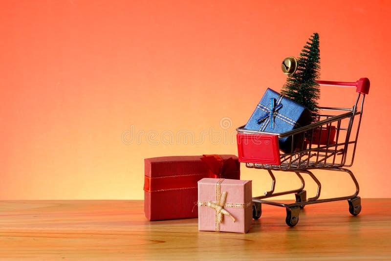 BEGREPPSMÄSSIGT NYTT ÅR med att shoppa spårvagnen, gåvaaskar och julgranen på en trätabell arkivbild