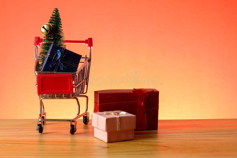 BEGREPPSMÄSSIGT NYTT ÅR med att shoppa spårvagnen, gåvaaskar och julgranen på en trätabell arkivfoton