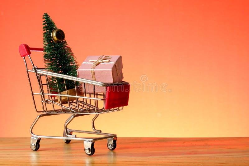 BEGREPPSMÄSSIGT NYTT ÅR med att shoppa spårvagnen, gåvaaskar och julgranen på en trätabell fotografering för bildbyråer