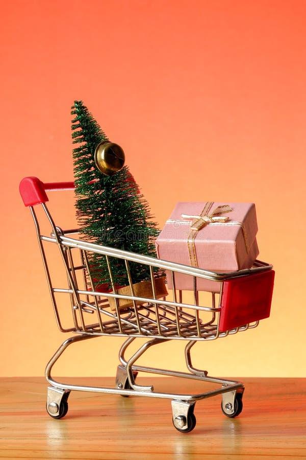 BEGREPPSMÄSSIGT NYTT ÅR med att shoppa spårvagnen, gåvaaskar och julgranen på en trätabell royaltyfri fotografi