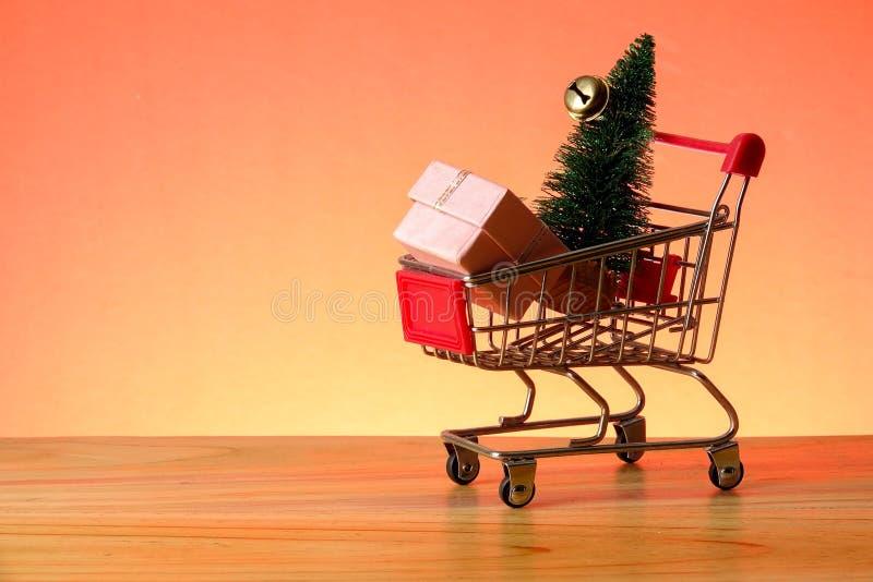 BEGREPPSMÄSSIGT NYTT ÅR med att shoppa spårvagnen, gåvaaskar och julgranen på en trätabell arkivfoto