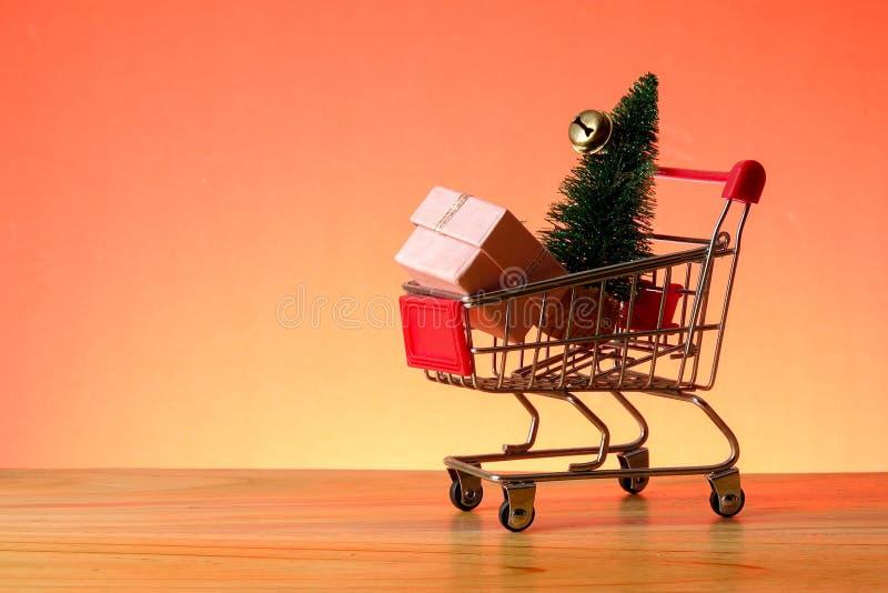 BEGREPPSMÄSSIGT NYTT ÅR med att shoppa spårvagnen, gåvaaskar och julgranen på en trätabell royaltyfria bilder