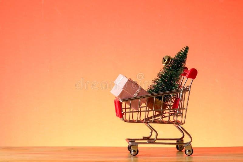 BEGREPPSMÄSSIGT NYTT ÅR med att shoppa spårvagnen, gåvaaskar och julgranen på en trätabell royaltyfria foton