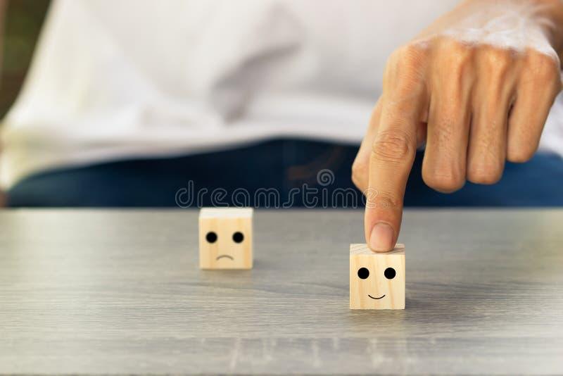 Begreppsm?ssigt reagerade kunden till granskningen Klienten som anv?nder handen, v?ljer den lyckliga framsidaleendesymbolen p? tr fotografering för bildbyråer