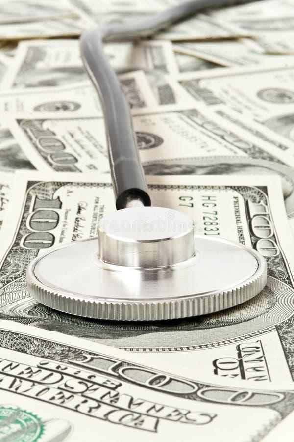 begreppsmedicinpengar över stetoskopet arkivbild