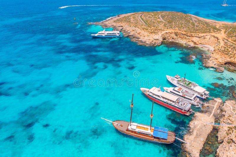 Begreppsparadissemester Den vita yachten med seglar i klart vatten av havet med sand Blå lagun Comino Malta flyg- sikt royaltyfria bilder