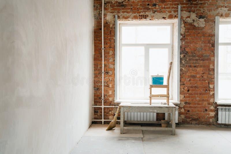 Begreppsreparation murbruk av fönster och väggar av röd tegelsten Stora fönster i rummet, en konstruktionsget, en stol och wi för fotografering för bildbyråer