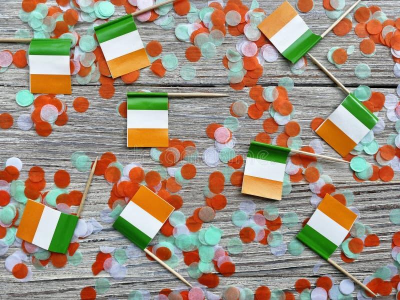 Begreppssjälvständighetsdagen för MARS 17 av Irland och Irland den nationella dagen mini- flaggor på vit träbakgrund med konfetti royaltyfri foto