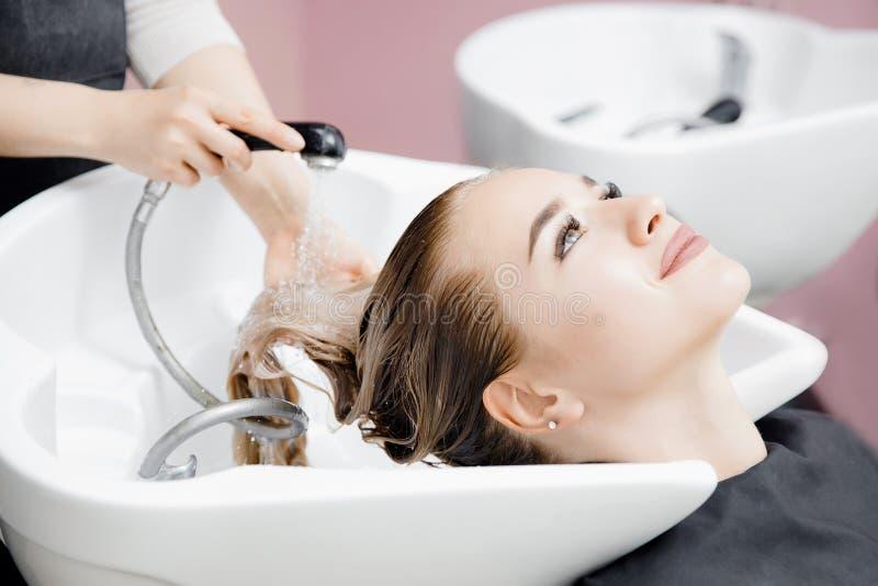 Begreppsskönhetsalong Frisören tvättar hår av den härliga blonda flickan under klappet tvättar sig in arkivbild