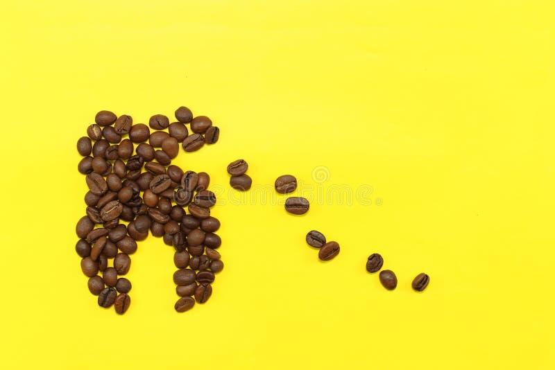 Begreppstanden av kaffekorn kollapsar under påverkan av kaffe royaltyfri bild