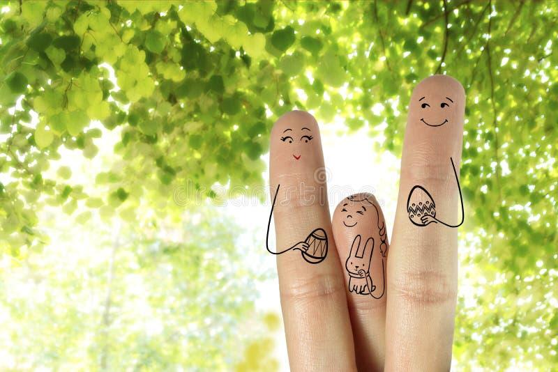 Begriffs-Ostern-Fingerkunst Familie halten gemalte Eier Tochter hält Häschen stockbilder