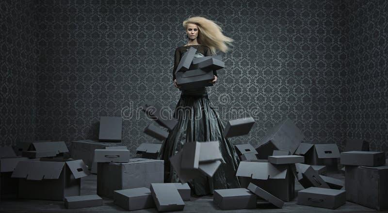 Begriffsbild einer blonden Dame unter vielen Kästen stockfotos