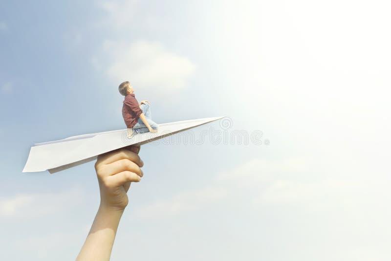 Begriffsbild eines kleinen Jungen, der vom Fliegen auf einem Papierflugzeug im Himmel träumt lizenzfreie stockfotos