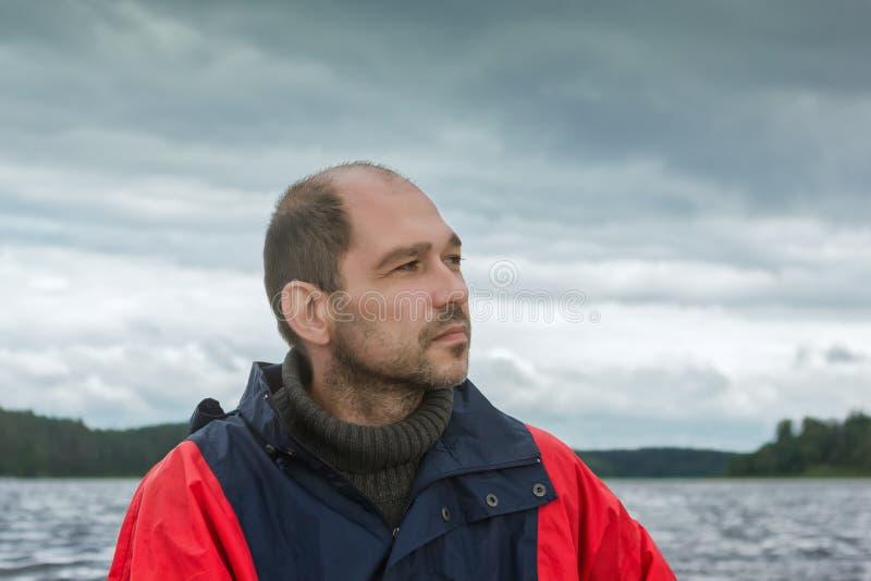 Begriffsporträt eines nachdenklichen bärtigen Mannes gegen einen bewölkten Himmel lizenzfreie stockfotografie