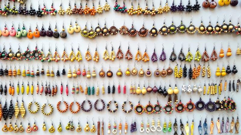 Begrip: de waarde van vakmanschap Veel handgemaakte gekleurde houten oorringen die in een rij te koop worden aangeboden royalty-vrije stock foto
