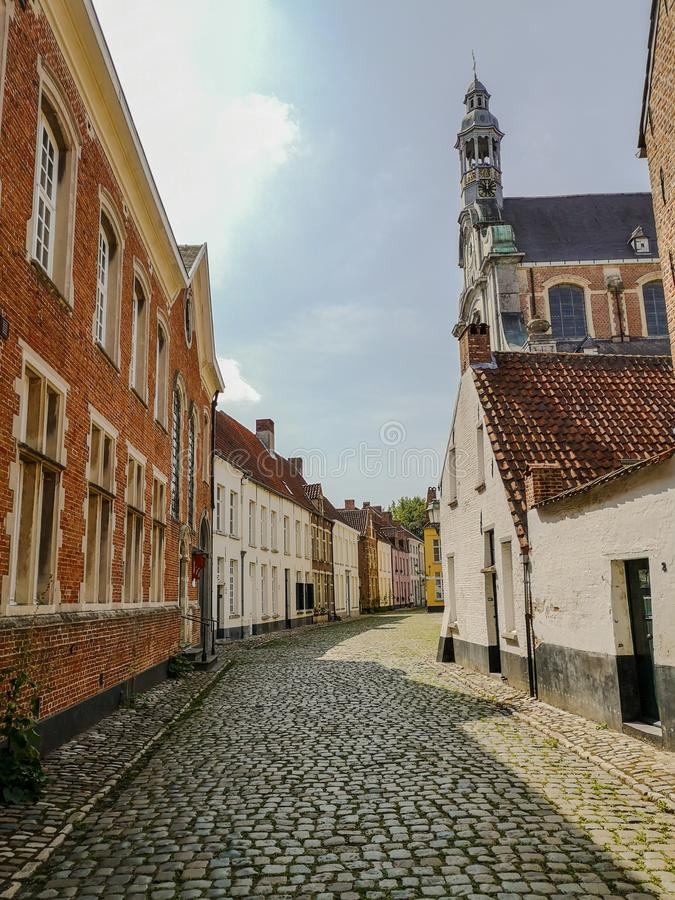 The beguinage and the St. Margaret`s church in Lier, Belgium. Narrow street with old houses and the St. Margaret`s church in the Unesco protected beguinage in royalty free stock photos
