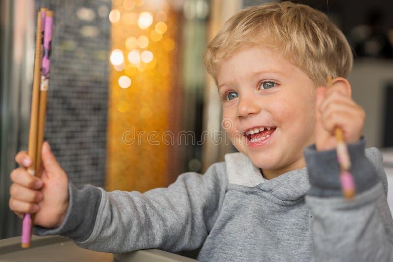 Begynnande pojke som ler med pinnar på restaurangen arkivfoto