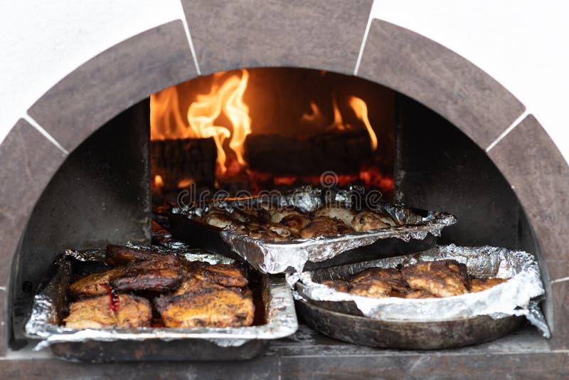 Behälter des gekochten Fleisches im Ofen auf den Kohlen lizenzfreies stockfoto
