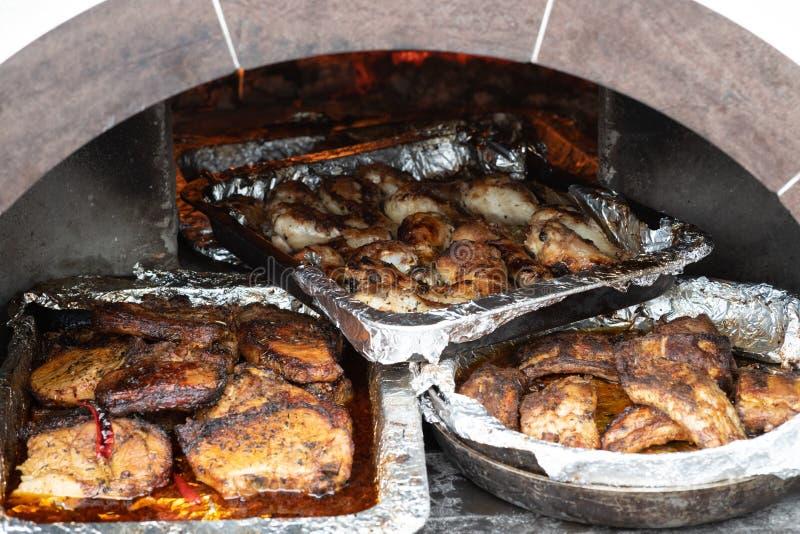 Behälter des gekochten Fleisches im Ofen auf den Kohlen stockfoto
