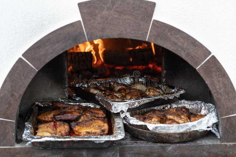 Behälter des gekochten Fleisches im Ofen auf den Kohlen stockbild
