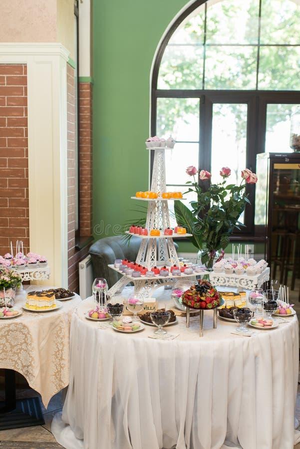Behälter für Kuchen in Form eines Eiffelturms Schokoriegel Viele Bonbons am Hochzeitsbankett lizenzfreie stockfotos