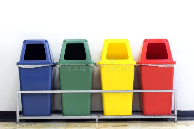 Behälter-, Grüne, Blaue, Gelbe und Rotepapierkörbe mit bereiten Abfallsymbol, Abfall mit vier bunten Papierkörben auf Wandweiß au stockfotografie