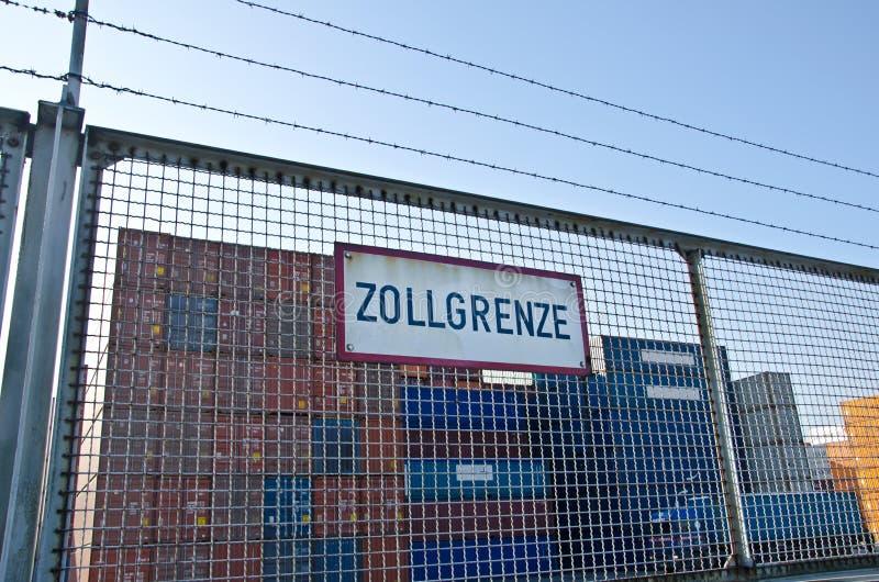 Behälter hinter einem Zaun mit einem Zeichen, das 'Zollschranke 'Zollgrenze auf Deutsch sagt lizenzfreie stockbilder