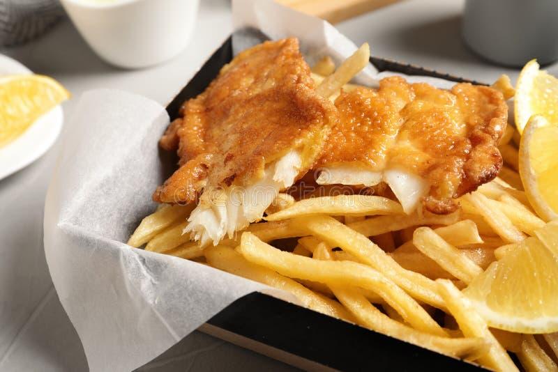 Behälter mit britischen traditionellen Fischen und Kartoffelchips lizenzfreie stockbilder