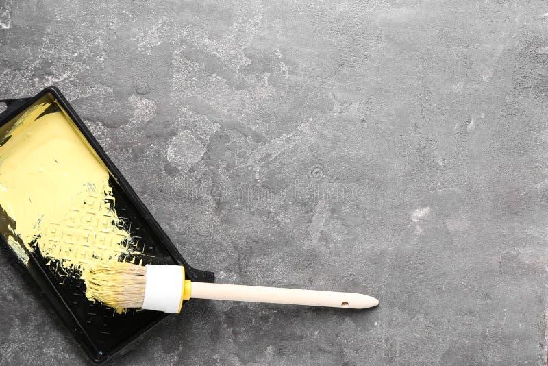 Behälter mit Farbe und Bürste für die Innenverzierung auf grauem Hintergrund lizenzfreies stockbild