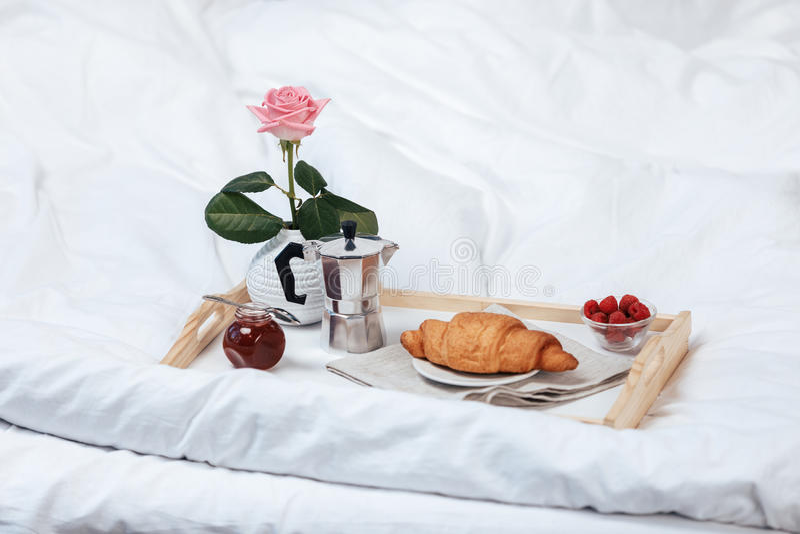 Behälter mit Frühstück auf Bett stockfoto