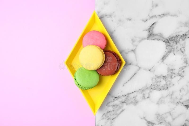 Behälter mit geschmackvollen frischen Makronen auf Farbhintergrund, Draufsicht stockfotos