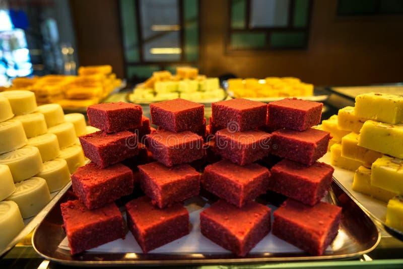 Behälter voll der indischen Süßspeise des bunten roten Samts des Stapels im Bäckereischaukasten stockfotografie