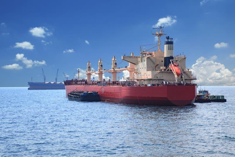 Behälterboots-Ladenwaren über klarem Gebrauch des blauen Wassers Seefür v lizenzfreie stockfotografie