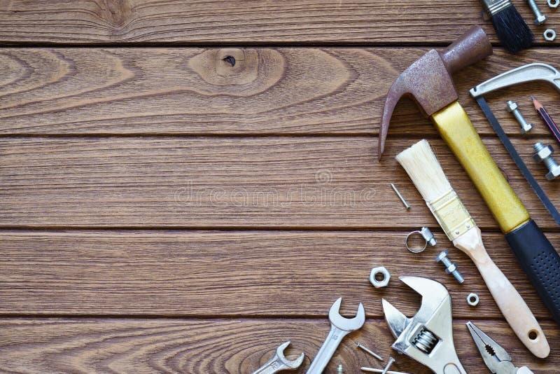 Behändiga hjälpmedel för variationer på träbakgrund Hammare såg, wrenche arkivfoton