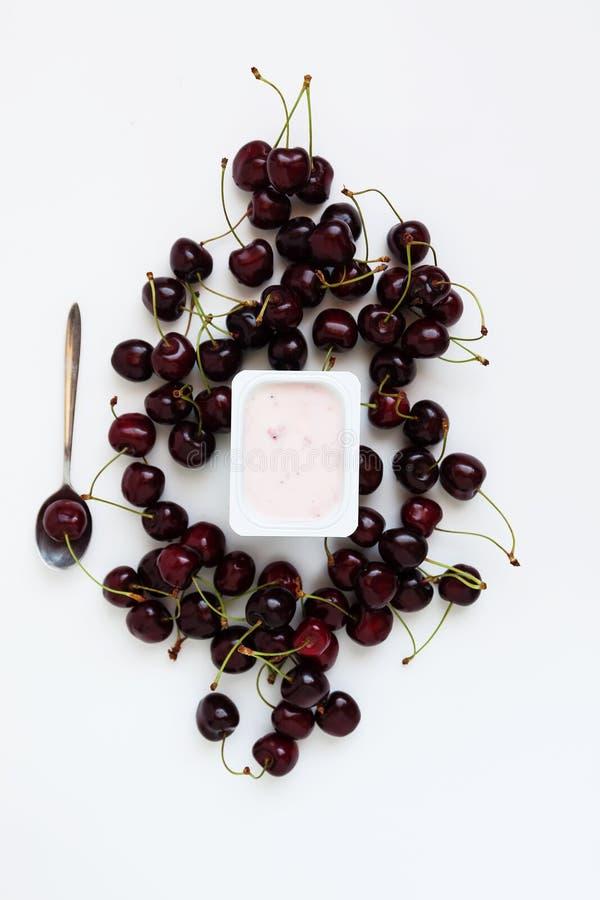 Behållare med yoghurt och en grupp av nya körsbärsröda bär på whi arkivfoto