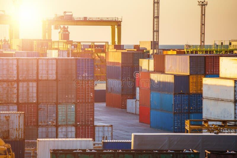Behållareaskar i lastfraktskepp och industriella portkranar på solnedgången Logistiska havstrans. och sändnings eller leverans arkivfoto