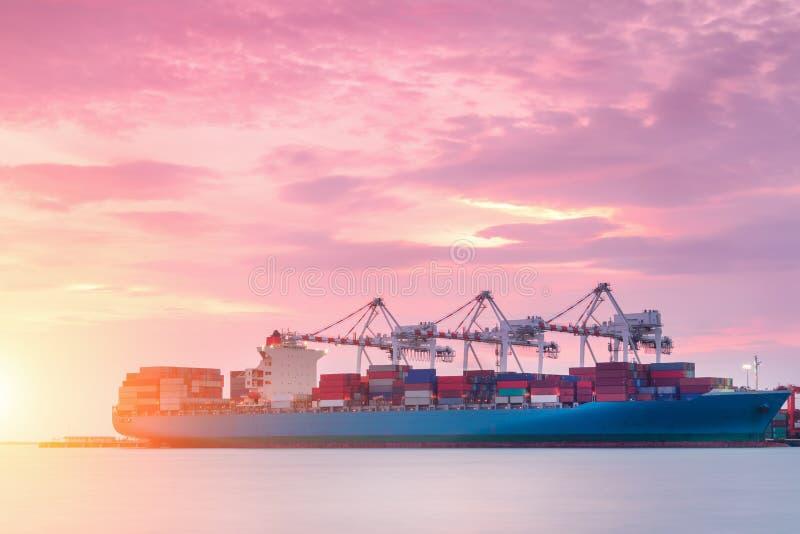Behållarelastfrakter sänder med den arbetande kranbron i skeppsvarv på skymning för logistisk importexport royaltyfria bilder