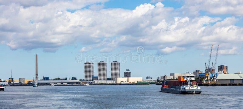 Behållareskepp och logistik mot Rotterdam cityscape arkivbild