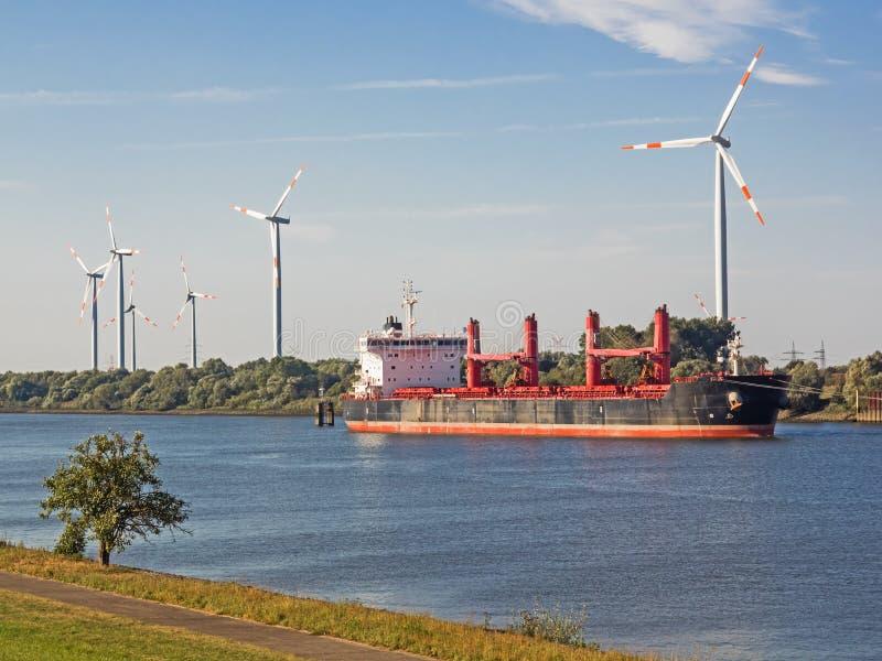 Behållareskepp på en flod med vindturbiner i bakgrunden royaltyfria foton