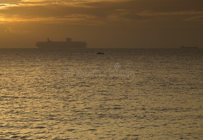 Behållareskepp silhouetted mot horisonten på soluppgång royaltyfri foto