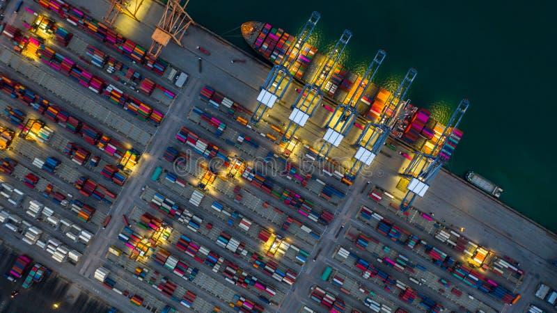 Behållareskepp som arbetar på den natt-, affärsimportexporten som är logistisk, och trans. av internationellt med behållareskeppe royaltyfri fotografi