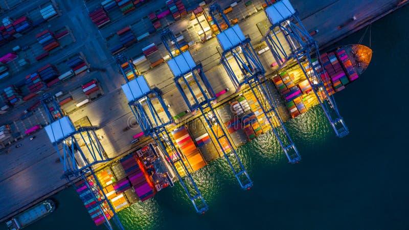Behållareskepp som arbetar på den natt-, affärsimportexporten som är logistisk, och trans. av internationellt med behållareskeppe royaltyfria foton