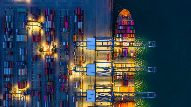 Behållareskepp som arbetar på den natt-, affärsimportexporten som är logistisk, och trans. av internationellt med behållareskeppe arkivfoto