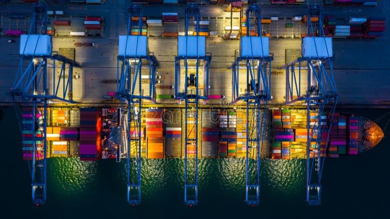 Behållareskepp som arbetar på den natt-, affärsimportexporten som är logistisk, och trans. av internationellt med behållareskeppe arkivbild