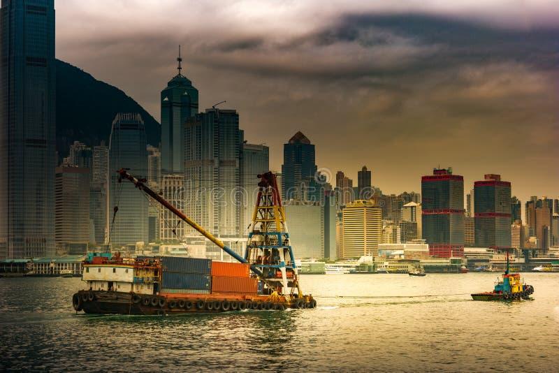 Behållareskyttel och ett litet bogserbåtfartyg - förtöja operationer i Hong Kong royaltyfria foton
