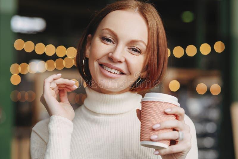 Behaarte Frau Browns mit bilden, das toothy Lächeln, gekleidet in der weißen Schildkrötenhalsstrickjacke, genießt heißes Getränk, stockbild