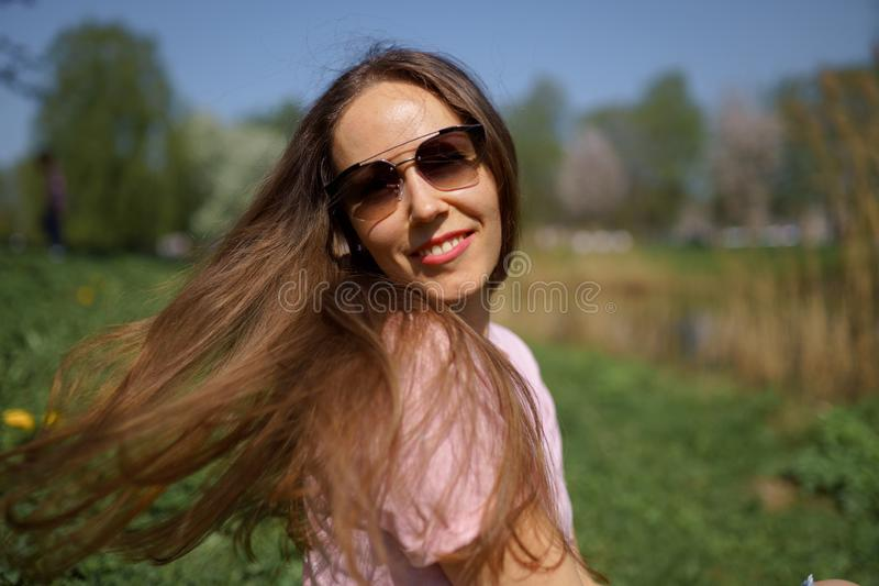 Behaartes Frauenm?dchen des jungen gl?cklichen Reisendbrauns, das herum in ein neues Bestimmungsland mit einer rosa Kirschbl?te l lizenzfreies stockfoto